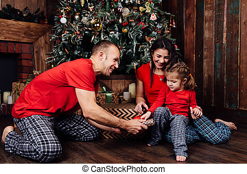family in pajamas plays next to a Christmas tree and a fireplace. A little daughter takes a gift from her father.
