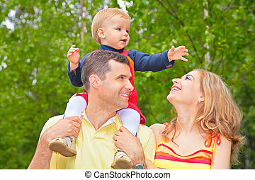 Family in park with child on shoulders