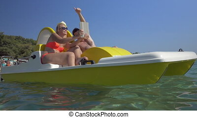 Family in pedal boat taking selfie with pad