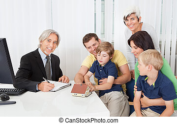 Family in real-estate agency talking construction planner