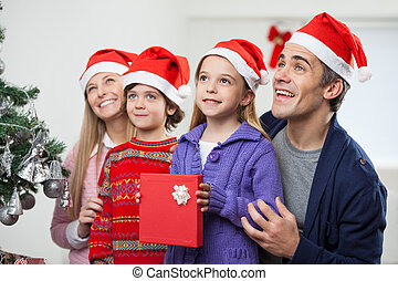 Family In Santa Hat With Christmas Present