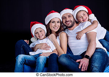 family in Santa hats looking at camera