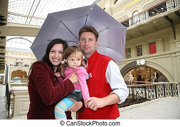 family in shop ith umbrella