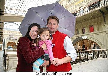family in shop ith umbrella