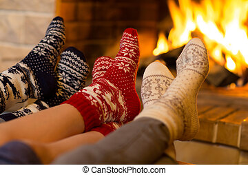 Family in socks near fireplace in winter or christmas time...