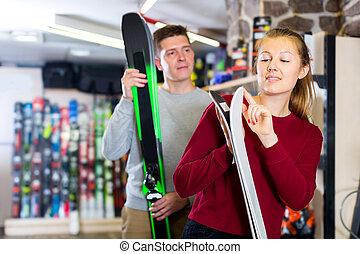 Family in sport equioment are choosing modern ski