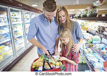 Family in supermarket aisle with full shopping basket