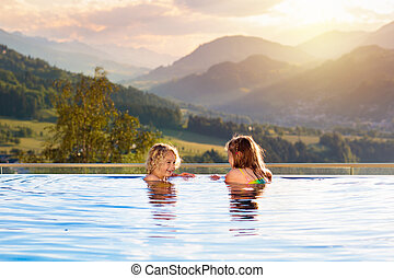 Family in swimming pool with mountain view