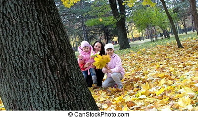 Family in the autumn park playing with leaves.
