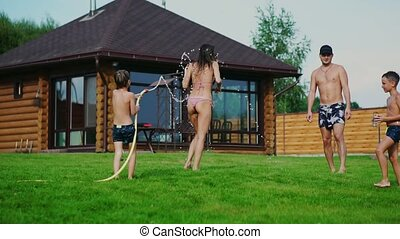 Family in the backyard of a country house in the summer relax playing with water and hosing