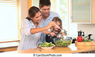 Family in the kitchen making a salad together
