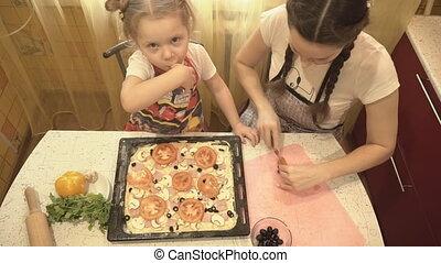 Family in the kitchen preparing pizza