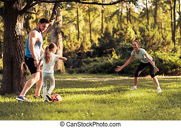 Family in the park playing football. Woman playing as goalkeeper