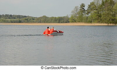 family in the pedalo boat on lake