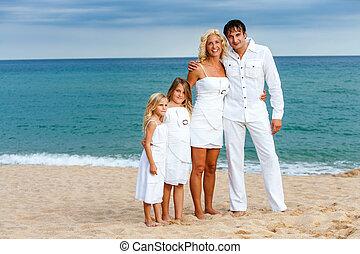 Family in white on beach.