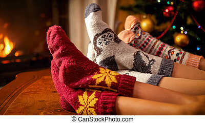Family in woolen socks holding feet on wooden table next to burning fireplace and Christmas tree