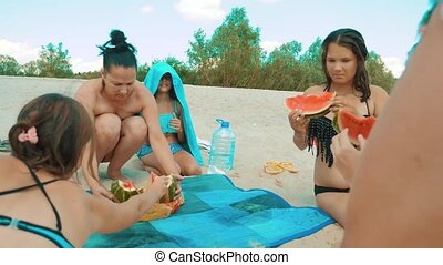 family is resting on the beach in the summer eating a watermelon slow motion video. girls in bathing suits eating watermelon. family summer vacation beach lifestyle concept