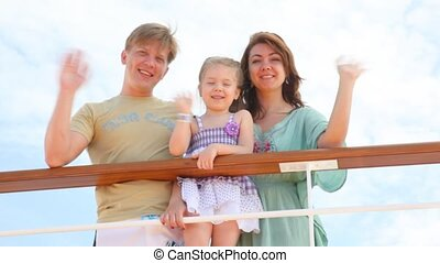 family is waving hands from the deck of cruise ship