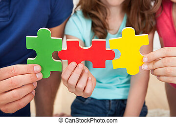 Family Joining Puzzle Pieces - Midsection of family joining...