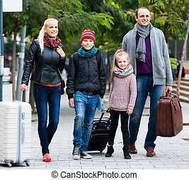 Family journey: spouses with children walking and luggage - ...
