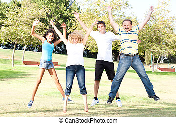 Family jumping high in the air on a green meadow