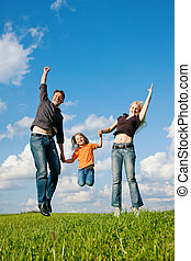 Family jumping on meadow in summer