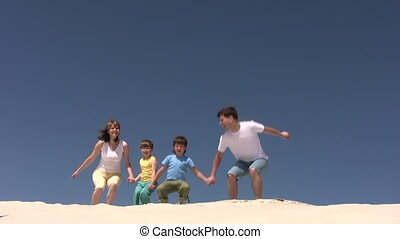 Family jumps on the sand