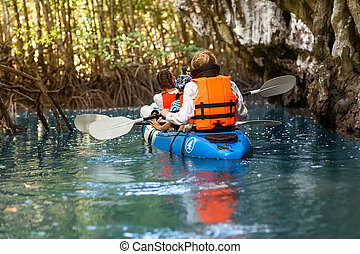 family kayaking through the jungle