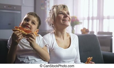 Family laughing, eating pizza and watching cartoon - Happy...