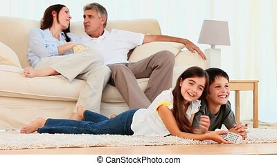 Family laughing in front of tv
