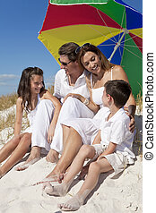 Family Laughing Under Colorful Umbrella On Beach