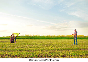 Family launches a kite in the field