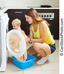 Family laundry. Woman with toddler loading clothes into the ...