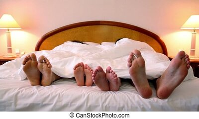 Family lay in bed under blanket and move bootless feet