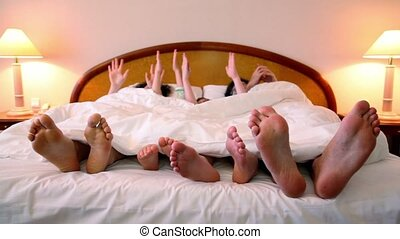 Family lay in bed under white blanket with barefoot feet and makes various gestures by hands