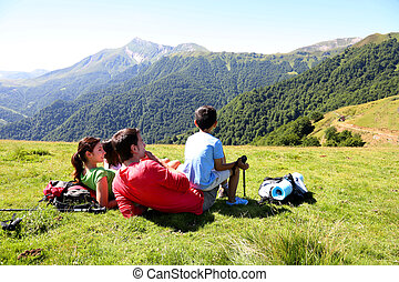 Family laying down the grass enjoying mountain view