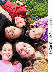 Family laying on the grass - Attractive muti-racial family...