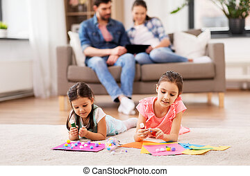 happy sisters doing arts and crafts at home