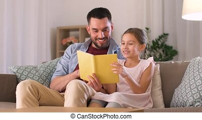 happy father and daughter reading book at home