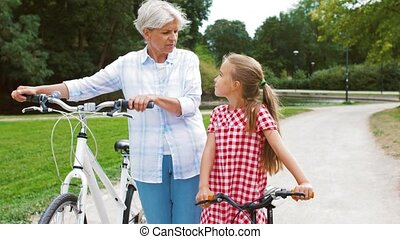 grandmother and granddaughter with bicycles - family,...