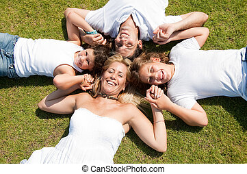 Family lies on grass