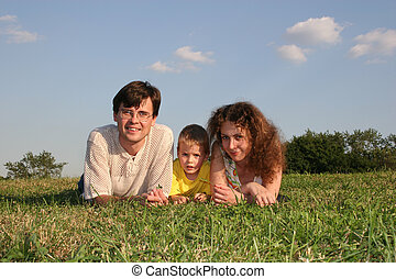 family lies on meadow