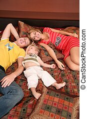 family lies on red carpet on sofa