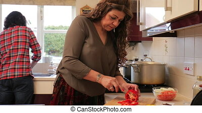 Family Life in the Kitchen - Mature woman is slicing peppers...