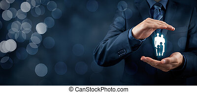 Family life insurance, family services and supporting families concepts. Businessman with protective gesture and silhouette representing young family. Wide banner composition with bokeh in background.