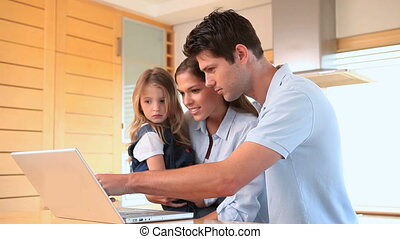 Family looking a laptop screen