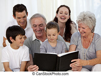 Family looking at a photograph album at home