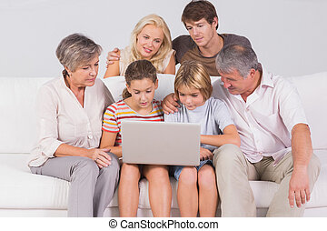 Family looking at laptop on couch