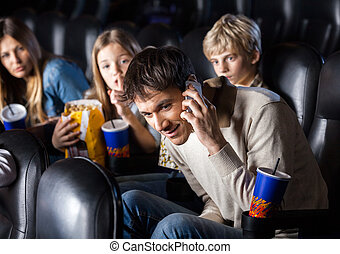 Family Looking At Man Using Mobilephone In Theater