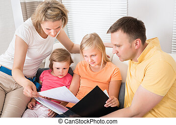 Family Looking At Photos In Photobook